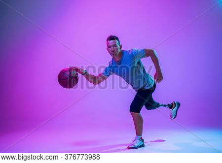 Athlete With Disabilities Or Amputee On Gradient Studio Background In Neon. Professional Male Basket