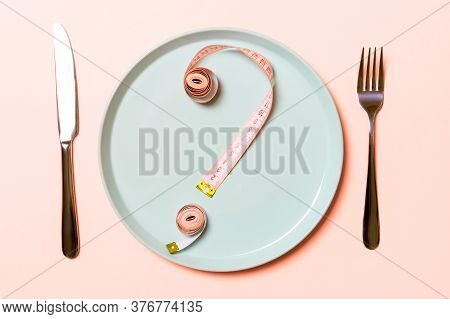 Question Mark Made Of Measuring Tape On Round Plate On Pink Background. Top View Of Hesitation And D