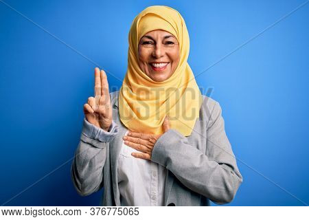 Middle age brunette business woman wearing muslim traditional hijab over blue background smiling swearing with hand on chest and fingers up, making a loyalty promise oath