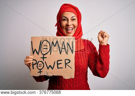 Middle age woman wearing muslim hijab asking for women rights holding banner screaming proud and celebrating victory and success very excited, cheering emotion