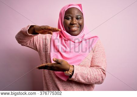 Young african american plus size woman wearing muslim hijab over isolated pink background gesturing with hands showing big and large size sign, measure symbol. Smiling looking at the camera. Measuring