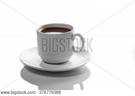 Small White Porcelain Cup With Hot Coffee On A White Saucer Side View Isolated On A White Background