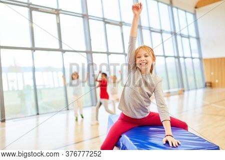 Happy girl exults in physical education in the gym of elementary school
