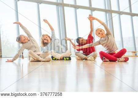 Pupils group in healthy stretching in physical education of elementary school