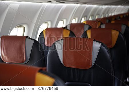 Empty Cabin Of The Plane. Soft Seats For Passengers, Portholes. Inside A Passenger Plane. A Seat On