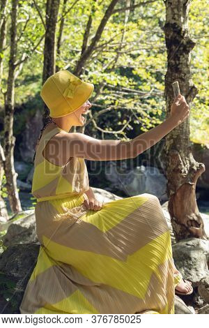 Beautiful woman sitting in the woods with a yellow dress and a phone