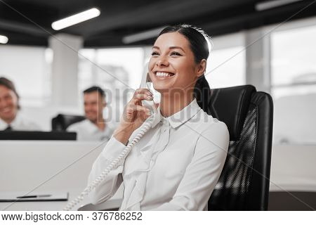 Happy Woman In White Shirt Smiling And Having Phone Conversation With Customer While Working In Cont