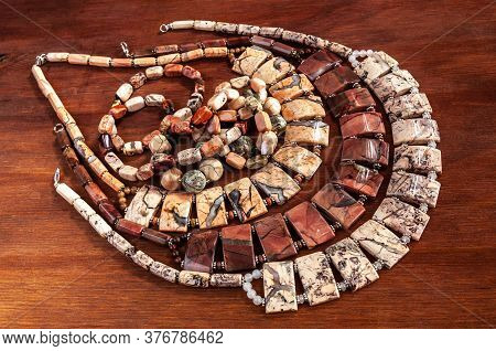 A Few Necklace Made Of Ural Jasper On Wooden Background
