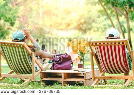 Backview Of Happiness Woman On A Summer Holiday Sitting On  Garden Chair To Relax In The Public Park