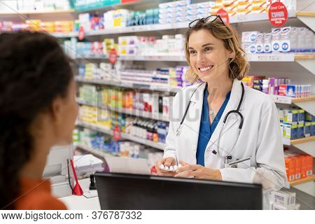 Pharmacist giving medicine to customer in modern pharmacy. Rear view of young woman buying analgesic at pharmacy. Happy doctor giving strip of tablet to customer.