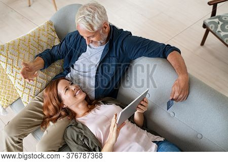 Top view of middle aged couple booking holidays online with a credit card. High angle view of mature woman lying on old man lap using digital tablet to buy on an ecommerce website, shopping online.
