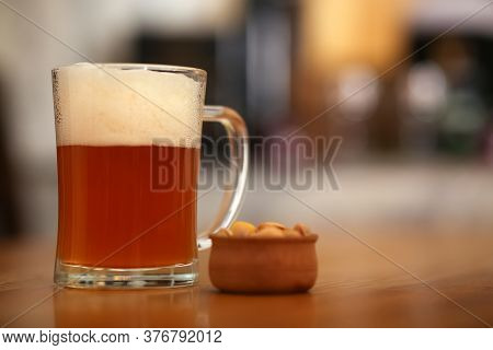 Pint Of Cold Tasty Beer Served With Peanuts On Wooden Table