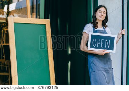 Young Female Owner Or Waitress In Apron Showing Chalkboard With Open Sign At The Coffee Shop. Local