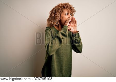 Beautiful african american woman with curly hair wearing casual sweater over white background Shouting angry out loud with hands over mouth