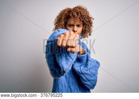 Young beautiful african american woman wearing turtleneck sweater over white background Punching fist to fight, aggressive and angry attack, threat and violence