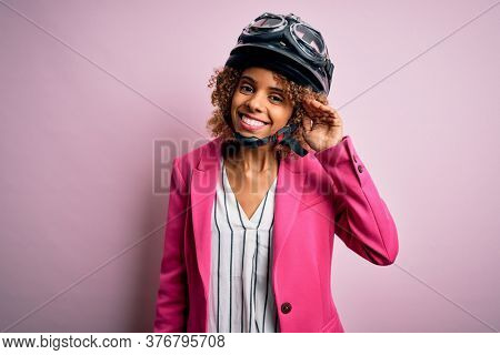 African american motorcyclist woman with curly hair wearing moto helmet over pink background smiling with hand over ear listening an hearing to rumor or gossip. Deafness concept.