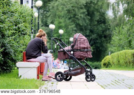 Woman With A Baby Stroller Sitting In A Summer Park With Smartphone. Concept Of Motherhood, Young Mo
