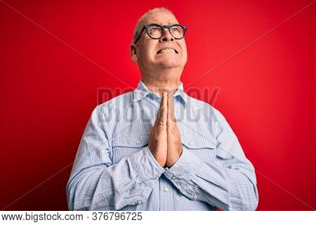 Middle age handsome hoary man wearing casual striped shirt and glasses over red background begging and praying with hands together with hope expression on face very emotional and worried. Begging.