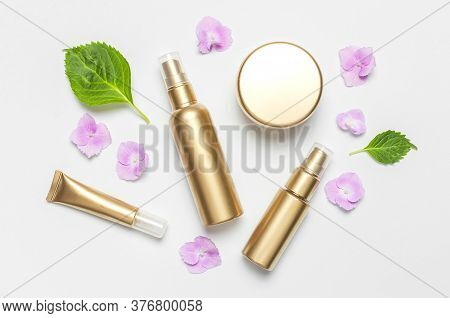 Cosmetic Mock Up Gold Bottles. Cosmetics, Pink Hydrangea Flowers On Light Background. Cosmetics Spri