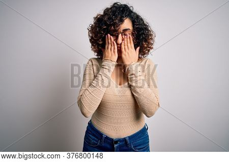 Young beautiful curly arab woman wearing casual t-shirt and glasses over white background rubbing eyes for fatigue and headache, sleepy and tired expression. Vision problem