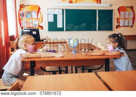 Two Schoolgirls In Medical Masks Are Sitting At A School Desk, Opposite Each Other, Group Session, B