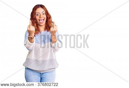 Young latin woman wearing casual clothes showing middle finger doing fuck you bad expression, provocation and rude attitude. screaming excited