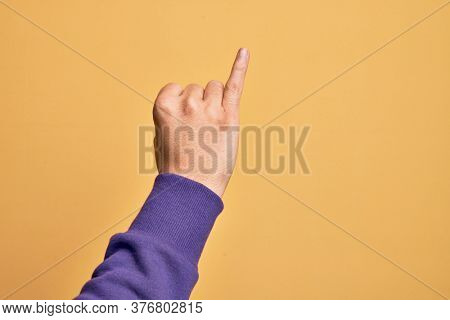 Hand of caucasian young man showing fingers over isolated yellow background showing little finger as pinky promise commitment, number one