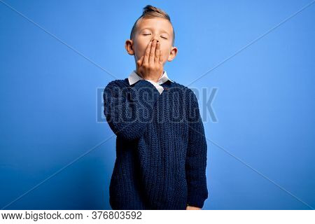 Young little caucasian kid with blue eyes wearing winter sweater over blue background bored yawning tired covering mouth with hand. Restless and sleepiness.