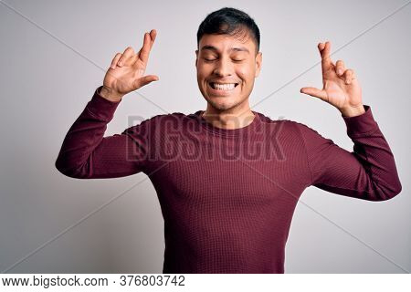 Young handsome hispanic man wearing casual shirt standing over white isolated background gesturing finger crossed smiling with hope and eyes closed. Luck and superstitious concept.