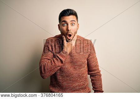 Young handsome man wearing casual sweater standing over isolated white background Looking fascinated with disbelief, surprise and amazed expression with hands on chin
