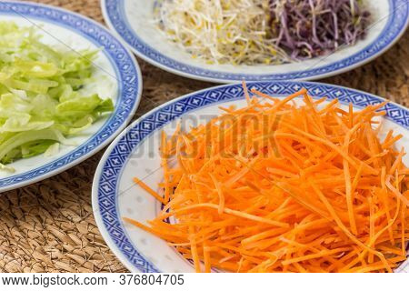 Raw Carrot, Alfalfa And Iceberg Lettuce Served On Chinese Plates