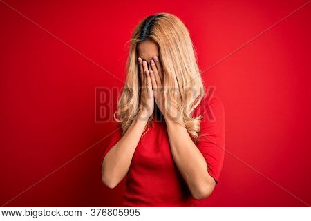 Young beautiful blonde woman wearing casual t-shirt standing over isolated red background rubbing eyes for fatigue and headache, sleepy and tired expression. Vision problem