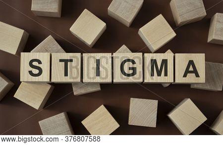 Stigma Word In Wooden Cube Against A Dark Background