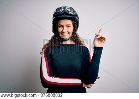 Beautiful motorcyclist woman with curly hair wearing moto helmet over white background with a big smile on face, pointing with hand and finger to the side looking at the camera.