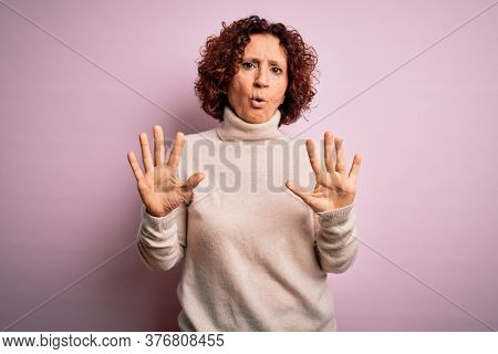 Middle age beautiful curly hair woman wearing casual turtleneck sweater over pink background Moving away hands palms showing refusal and denial with afraid and disgusting expression. Stop.