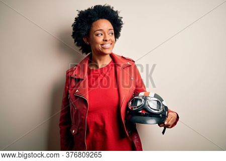 Young African American afro motorcyclist woman with curly hair holding motorcycle helmet smiling looking to the side and staring away thinking.
