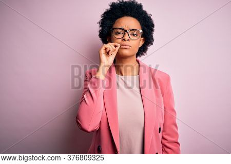 Young beautiful African American afro businesswoman with curly hair wearing pink jacket mouth and lips shut as zip with fingers. Secret and silent, taboo talking