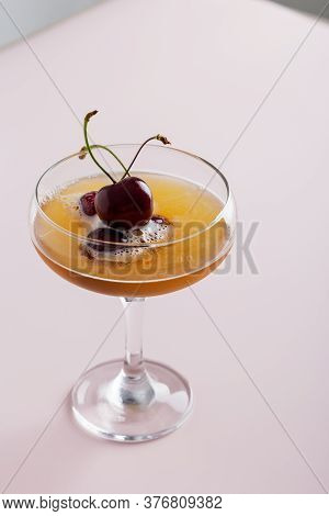 Minimal Cocktail Drink With Sweet Cherry In Glass At Pink Background. Concept Of Garnished Cocktail