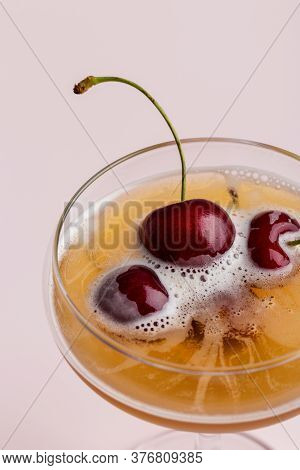 Close Up Minimal Cocktail Drink Garnished By Sweet Cherry At Pink Background