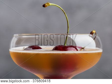 Sweet Cherry In Glass With Cocktail At Gray Background Close Up. Concept Of Sweet Alcohol Beverages