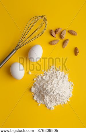Ingredients For Homemade Pie At Minimal Background. Flour, Eggs, Almonds And Whisk At Yellow Backgro