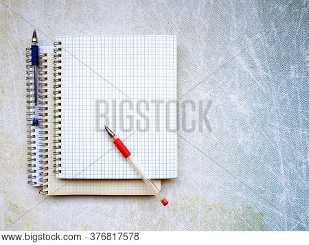 Three Notebooks Are On Top Of Each Other. There Is A Red Pen Diagonally On A Blank Sheet Of Paper. T