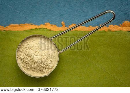 ashwagandha root (aka Indian ginseng) powder in a measuring metal scoop against handmade paper, superfood concept