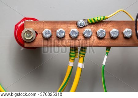 Cables Connected To A Copper Ground Bus Against A Light Wall. Horizontal Orientation.