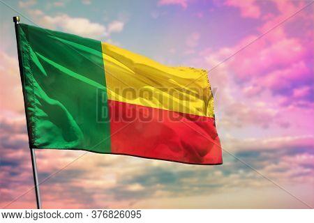 Fluttering Benin Flag On Colorful Cloudy Sky Background. Benin Prospering Concept.