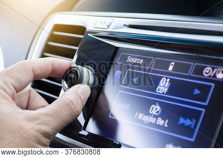 Driver Turning Volume Button Of Car Radio In A Car