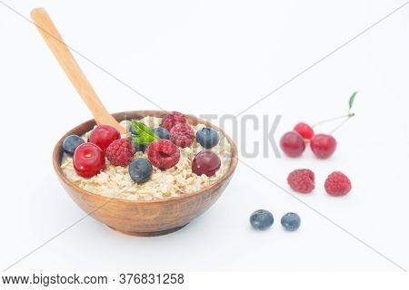 Rolled Oats With Blueberries And Raspberries On White Background. Healthy Breakfast Cereal Oat Flake