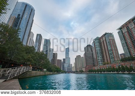 Tall Chicago Buildings Converge Toward Distant Buildings Along River From Level Of River.