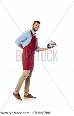 Bearded Waiter In Apron Holding Metal Dish Cover And Tray While Smiling At Camera On White Backgroun