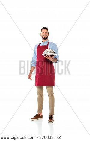 Handsome Smiling Waiter Holding Metal Tray And Dish Cover On White Background